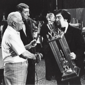 Charles Ursitti (right) shaking Willie Mosconi's hand while Howard Cosell looks on.